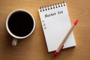 Coffee, red pen, and bucket list note pad